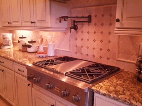 kitchen with gas stove faucet and tile backsplash