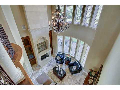 Luxury Mediterranean Estate For Sale in Odessa, FL:  Two Story Living Room with Fireplace and Rows of Windows