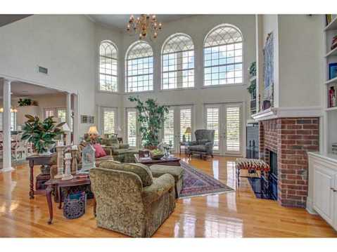 Beautiful Brick Estate for Sale in Odessa:  Two-Story Living Room with Fireplace and Rows of Windows